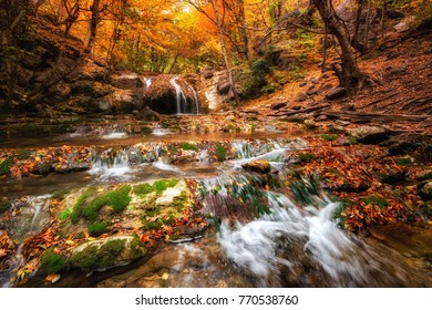 Scenic view autumn landscape with beautiful waterfall at mountain river in the forest with. Stones with moss in the water. Blurred water.