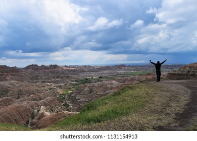 Scenic view of Badlands National Park in South Dakota with middle aged man enjoying the view.  Colorful oranges and green, blue cloudy sky.