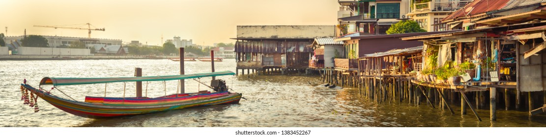 Scenic view of Bangkok riverside, Thailand. Boat and  slums on stilts on the foreground. Panorama
