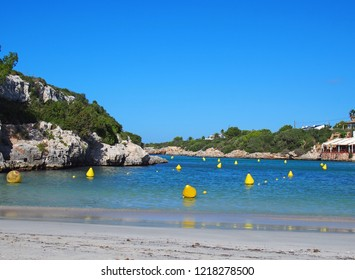 scenic view of the beach and bay at Cala Santandria in Menorca with yellow boat markers in a bright blue sunlit sea and surrounding rocks