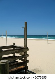 A scenic view of a beautiful beach with clear blue sky. There is a shower to rinse off the sand.