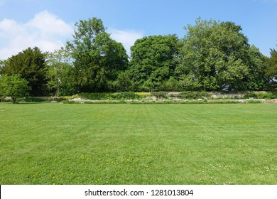 Scenic View of a Beautiful English Style Garden with a Large Open Green Grass Lawn, Leafy Trees and a Blue Sky Above