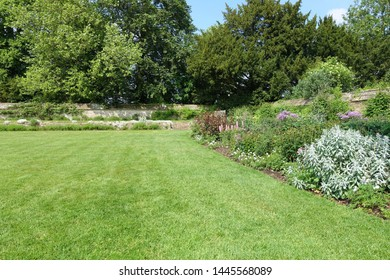 Scenic View of a Beautiful English Style Landscape Garden with a Green Mowed Lawn and Colourful Flower Bed in Bloom