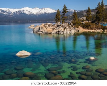 Scenic view of beautiful Lake Tahoe in Spring, landscape of the United States of America, clear water, nice sky,  stone island, tree, fresh air and snow mountains