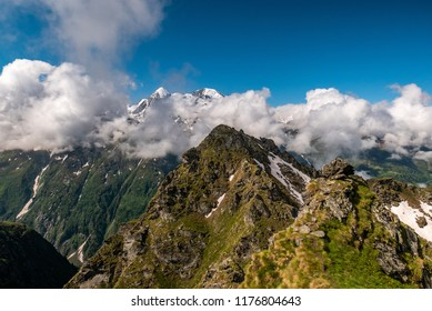 Scenic view of beautiful landscape in Swiss Alps. Fresh green meadows and snow-capped mountain tops in the background in springtime, Switzerland.