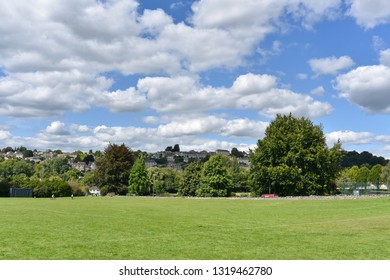 Scenic View of a Beautiful Large Lush Green Playing Field Lawn in a Town Park with White Fluffy Clouds Above
