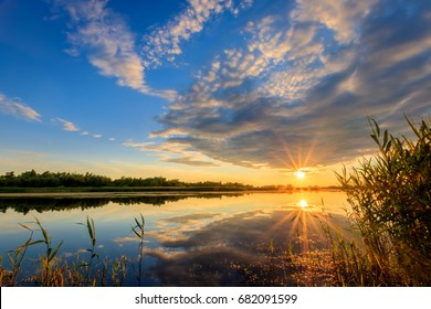 Scenic view of beautiful sunset above the pond at summer with cloudy sky background.