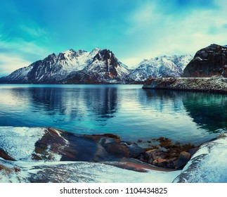Scenic view of beautiful winter lake with snowy mountains at Lofoten Islands in Northern Norway