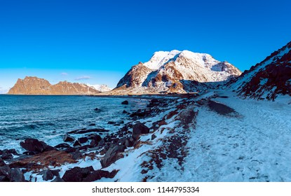 Scenic view of beautiful winter sea scandinavian landscape with blue sky, mountains and snow at Lofoten Islands in Northern Norway