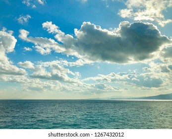 Scenic view of blue sea against blue sky and clouds