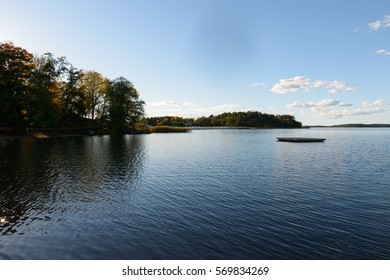 Scenic view of calm river and clear blue sky with autumn forest along the riverside at Naantali Finland