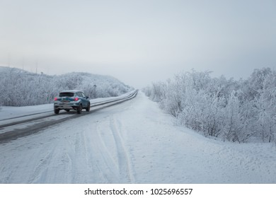 scenic view of car and road with snow covered landscape on cloudy winter day.