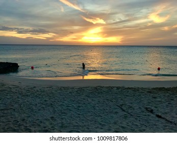 Scenic view of the Caribbean sea at sunset with a silhouette of a person in the beach of Boca Catalina, Aruba.
