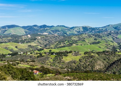 A scenic view of Carmel Valley, in Monterey County of central California, with rolling hills dotted with ranches and grass covered hills.