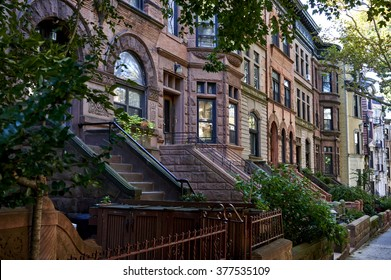 Scenic view of a classic Brooklyn brownstone block with a long facade and ornate stoop balustrades on a summer day in New York City.