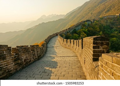 Scenic view of the cobblestone path on top of the Great Wall at golden sunrise. Beautiful autumn morning sunshine illuminates the Great Wall of China and the breathtaking forest covered landscape.