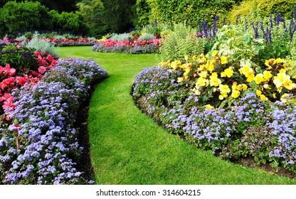 Farbige Blumenbeete und eine Rasenfläche mit Windung in einem attraktiven englischen Garten