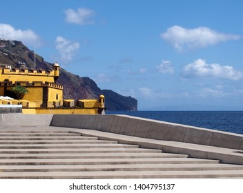 a scenic view of concrete steps on the seafront in funchal with a view of the ocean cliffs and Sao Tiago yellow fort with blue cloudy sky