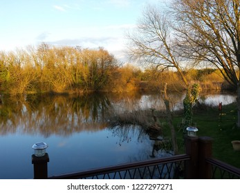 Scenic view from a deck over a gorgeous lake with beautiful reflections of the sky and trees showing rich tones in Lincolnshire, England.