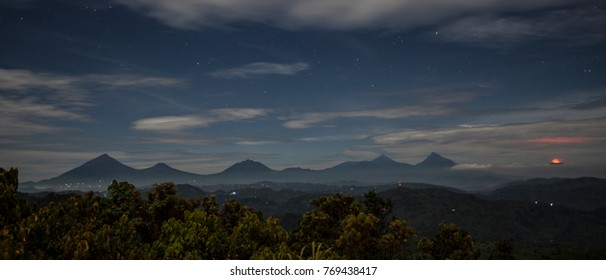 Scenic view of a distant volcano erupting in Volcanoes National Park, which stretches across Rwanda and Congo, at night under a starry sky
