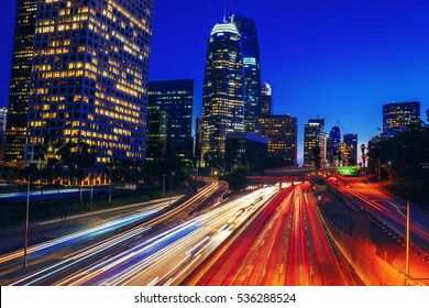 Scenic view of Downtown Los Angeles California at night overlooking busy freeway with light trails