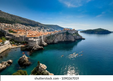 Scenic view of Dubrovnik city wall and old town  situated along the coast with Lokrum island and kayak activities on  Adriatic sea