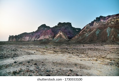Scenic view of famous colorful Rainbow Valley Mountains on Iranian Hormuz Island, Hormozgan Province, Persian Gulf, Iran. Colorful rocky salty volcanic background and blue sky.