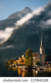 Scenic view of famous Hallstatt lakeside town reflecting on Hallstattersee lake in the Austrian Alps in morning light in autumn with bushes and flowers on the foreground, Salzkammergut region, Austria