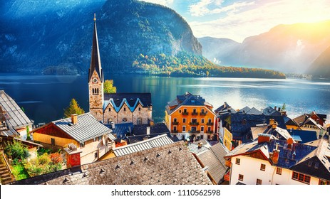 Scenic view of famous Hallstatt mountain village with Hallstatter lake. Sunny autumn sunrise on Hallstatt lake. Location: resort village Hallstatt, Salzkammergut region, Austria, Alps. Europe.