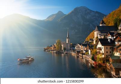 Scenic view of famous Hallstatt mountain village in the Alps with traditional passenger ship at autumn morning. UNESCO World Heritage Hallstatt-Dachstein Salzkammergut, Upper Austria