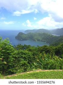 A scenic view of the famous Maracas Bay beach in Trinidad and Tobago from the Maracas lookout point. The deep blue Caribbean Sea interwoven between lush green trees & mountains.