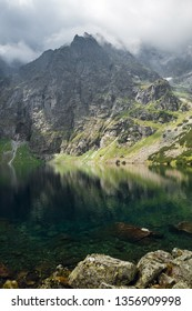 Scenic view of foggy mountains cover by dark clouds and green forest with a reflection in a lake. Stony shore. Morskie Oko. Marine Eye. High Tatras, Zakopane, Poland