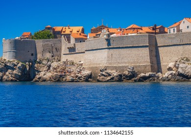 Scenic view of fort of St. Lawrence, the historical harbor and a small pier with a hill house area viewed from the sea level, Dubrovnik old town, Croatia, Europe