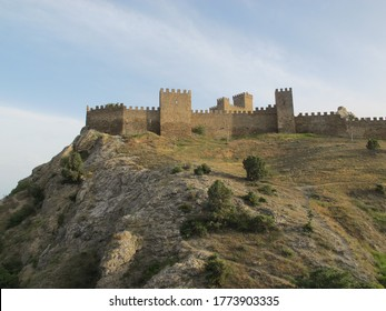 Scenic view of the Fortress mountain, covered with shrubs and faded grass in the sun and an ancient fortress with a defensive wall and towers on a warm summer evening. Genoese fortress, Sudak, Crimea