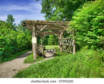 Scenic View Of Garden Arbor With Benches.