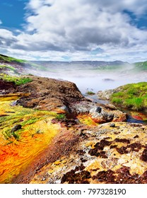 Scenic view of a geothermal area with very colorful deposits, a steaming hot water lake, in the background a mountain range, above a blue sky with a cloud formation. Iceland, Hengill area