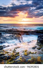 Scenic view of golden sunset and cloudscape over rocky coastline, Reunion Island.