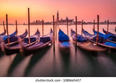 Scenic view of gondolas and San Giorgio Maggiore basilica in Venice at colorful sunrise, Italy