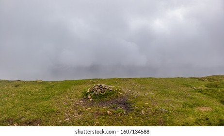 A scenic view of a grassy mountain summit with a stony cairn under a misty cloudy sky