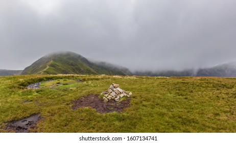 A scenic view of a grassy mountain summit with a stony cairn and mountain range in the background under a misty cloudy sky