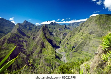 Scenic view of green mountains in Reunion Island National Park with blue sky and cloudscape background.