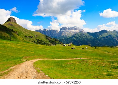 Scenic view of green plateau in high mountains with hotels and ski lift.