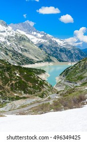 Scenic view from the Grimsel Pass in Switzerland down to the turqoise lake with the dam.