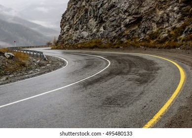 Scenic view of the hairpin bend wet winding road through the pass, part of the mountain serpentine in autumn cloudy weather with fog