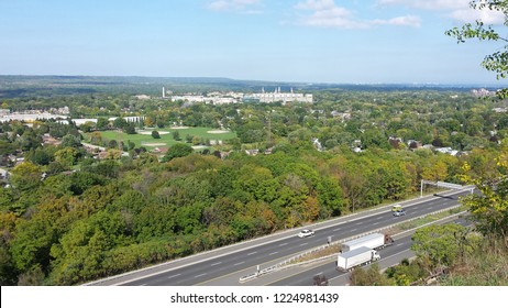 Scenic view from Hamilton Mountain in Ontario, Canada showing a highway with transport trucks and offering a brilliant view of the landscape below.