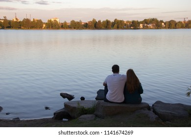 Scenic view with a happy young couple sitting on the stones in the foreground with a blurred out swedish lake Trummen in Vaxjo and enjoy the view in the region Smaland, Sweden with sunset