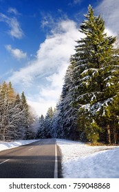 Scenic view of a highway in the Bavarian Alps with pine forest in winter. Sunny snowy day in the mountains.