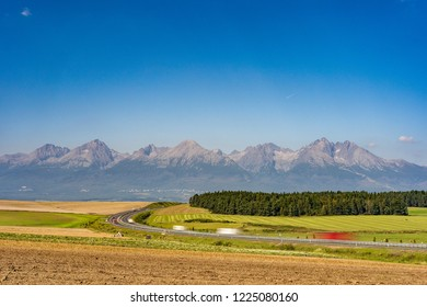Scenic view of highway leading to rocky peaks of High Tatras mountains, Slovakia summer day.