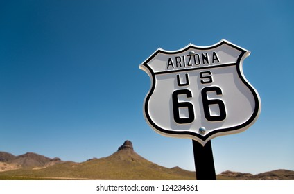 A scenic view of a historic Route 66 sign with a sky blue background