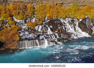 A scenic view of the Hraunfossar waterfalls, located near Husafell and Reykholt in West Iceland. Hraunfossar run down a series of rock steps from the Hallmundarhraun lava field into the Hvita River